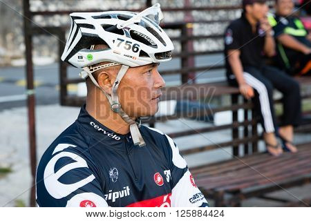 TANAH RATA, MALAYSIA - CIRCA FEBRUARY, 2015: Attractive man in the outfit cyclist at the stadium in the small town of Tanah Rata, mountainous area Cameron Highlands.
