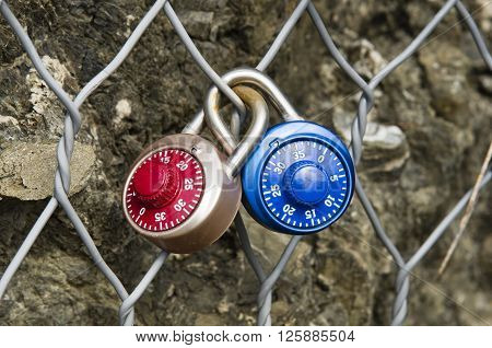 Two colored locks numerical combination closed on a metal grid one inside the other