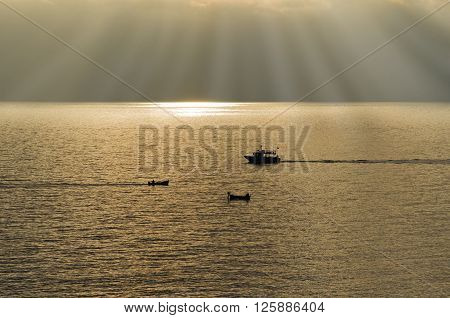 Cinque Terre Liguria Italy boats backlit cross at sunset on the bottom the sun's rays pass through the clouds