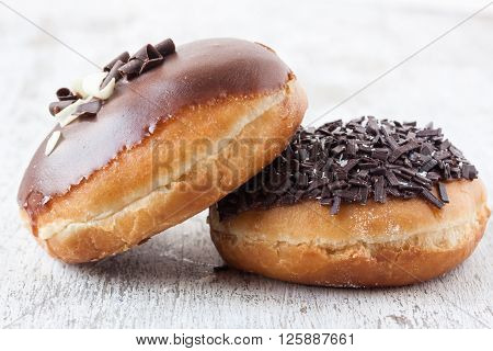 donuts with chocolate on a white wooden background