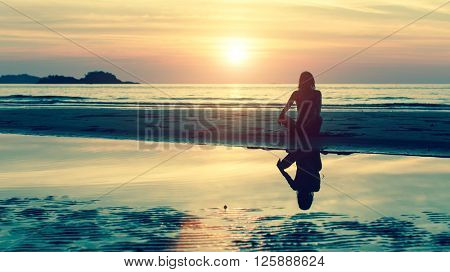 Silhouette of young girl in yoga pose sitting on the beach during amazing sunset.
