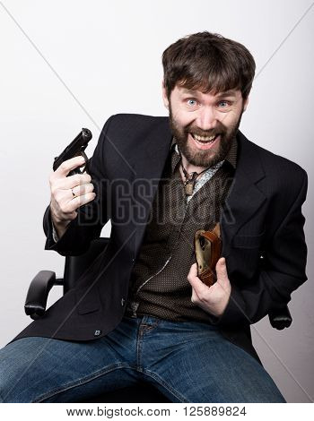 jolly bearded man in a jacket and jeans, sitting on a chair and holding a gun. gangster concept.