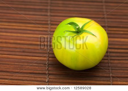 Green Tomato On A Bamboo Mat
