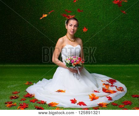 Young and beautiful bride with the flower bouquet and  falling red maple leaf the green background