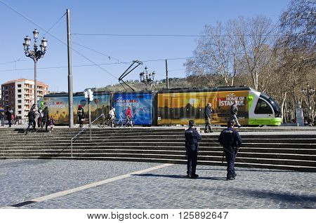 Bilbao Spain - March 27 2016: Local electric tramway with advertising to travel to Turkey on the square two policemen