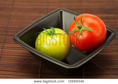 Green And Red Tomatoes In A Bowl On A Bamboo Mat