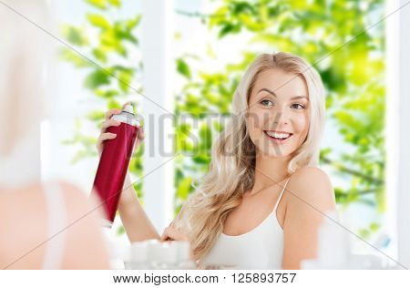 beauty, hygiene, hairstyle, morning and people concept - smiling young woman with hairspray styling her hair and looking to mirror at home bathroom over green natural background
