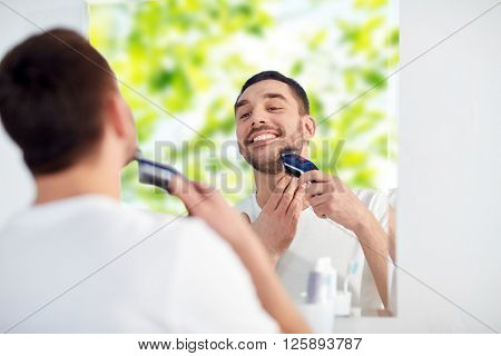 beauty, hygiene, shaving, grooming and people concept - young man looking to mirror and shaving beard with trimmer or electric shaver at home bathroom over green natural background