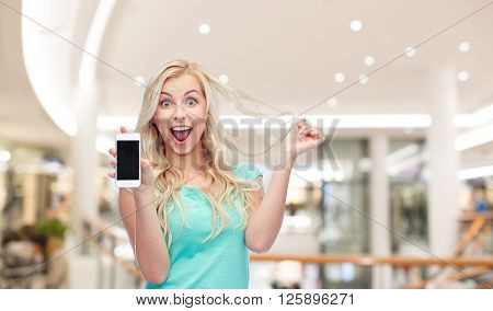 emotions, expressions, technology and people concept - smiling young woman or teenage girl showing blank smartphone screen over mall or shopping center background