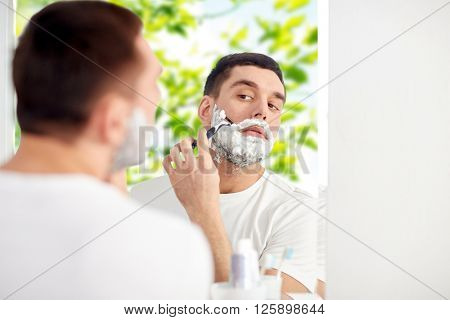 beauty, hygiene, shaving, grooming and people concept - young man looking to mirror and shaving beard with manual razor blade at home bathroom over green natural background