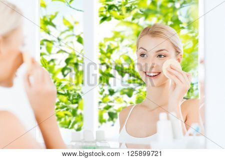 beauty, skin care and people concept - smiling young woman washing her face with facial cleansing sponge at bathroom over green natural background