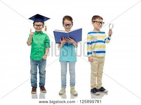 childhood, education, knowledge and people concept - happy little children in eyeglasses with book, magnifying glass and mortar board