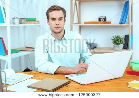 IT company. Young programmer working with laptop. Nice office interior. Professional coder looking at camera