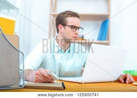 IT company. Young programmer working with laptop. Nice office interior. Professional coder looking at laptop and holding mobile phone
