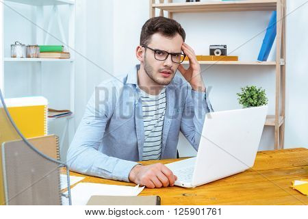IT company. Young programmer working with laptop. Nice office interior. Professional coder having headache