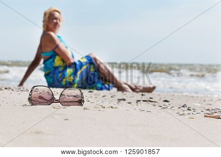 Sunglasses on the sand  and beautiful woman with blue sarong, sitting on thel beach