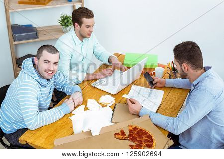 IT company. Young programmers working with laptop with pizza. Nice office interior. One professional coder looking at camera and smiling