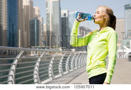 fitness, sport, people and healthy lifestyle concept - woman drinking water after doing sports over dubai city street or waterfront background