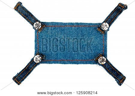 Frame with four straps jeans and rhinestones lies on the dark denim isolated on white background