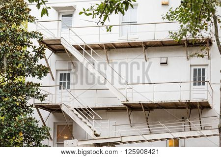 White Metal Fire Escape on Old White Building by trees