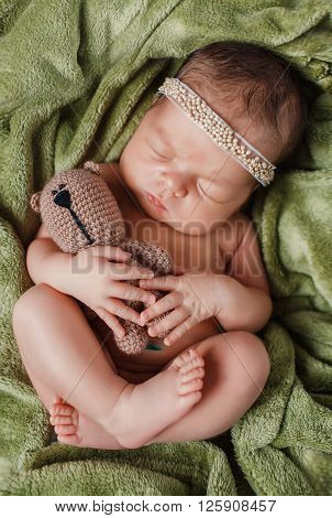 Peaceful sleep of a newborn baby on green bed hugging a stuffed animal,a cute kid who wore a wreath on his head, sleeping sweetly tucked arms and legs on a green blanket hugging brown Teddy bear