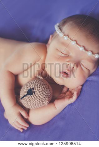 Peaceful sleep of a newborn baby on blue blanket hugging plush toy, a cute baby, who wore a wreath on his head, sleeping sweetly placing his hand on the cheek on a blue background