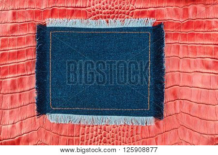 Frame made of denim with a fringe is on the red crocodile skin with space for your text