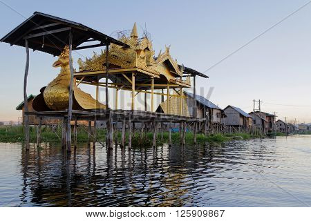 INLE LAKE MYANMAR - December 15 2014 : Golden bird on Inle lake. Inthar people which populates the region built on the water its houses on piles and lives on generative culture of fruits vegetables and flowers on incredible floating islands