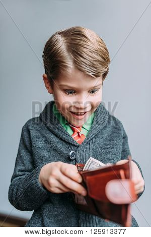 Young handsome guy looking happy while going through wallet smiling
