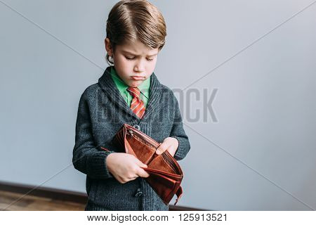 A close-up portrait of a shocked, surprised speechless boy, businessman holding an empty wallet