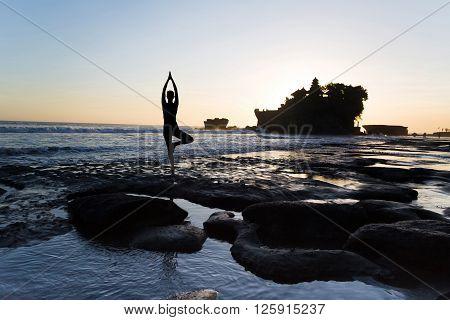 Vrikshasana tree pose from yoga by woman silhouette on sunset near Tanah lot temple