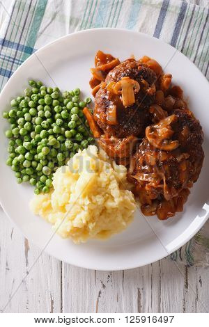 Salisbury Steak With Potatoes And Green Peas Close-up. Vertical View From Above