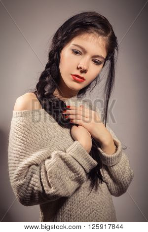 sensual sad girl with black plait on gray background