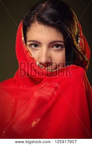 smiling girl in red hijab looks at camera