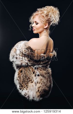 Jewelry and Fashion lady. Beautiful Woman wearing in Luxury Fur Coat over. Portrait of a woman in Studio on a black background in furs, luxury makeup, luxury bust. Advertise a fur coat from a lynx.