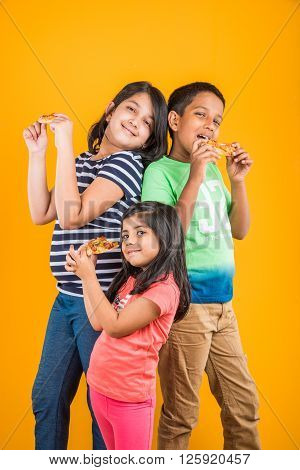 two indian girls and one boy eating pizza over yellow background