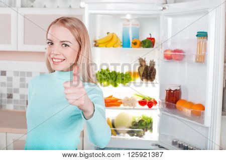 Pretty blonde standing near open fridge full of food. Young woman looking at camera, smiling and showing thumb up