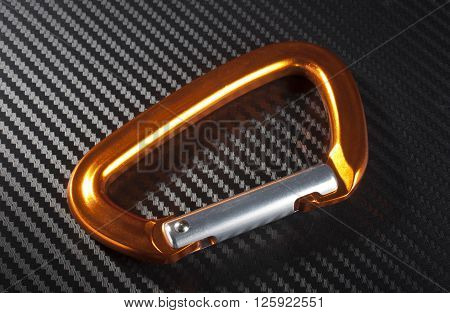 Orange carabiner made for climbing on a graphite background