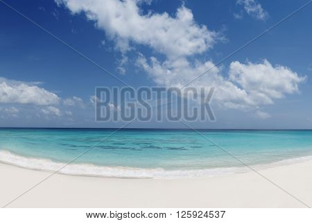 tropical beach with white sand turquoise water and blue cloudy sky