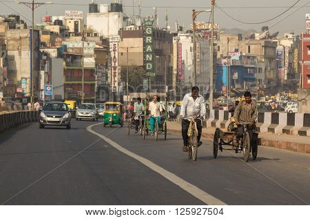 DELHI INDIA - 19TH MARCH 2016: A view along roads in Delhi during the day showing buildings Tuk Tuks rickshaws cars and people.