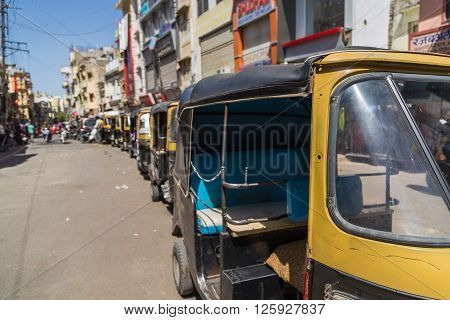 UDAIPUR INDIA - 20TH MARCH 2016: A queue of Rickshaws in central Udaipur during the day. People can be seen.
