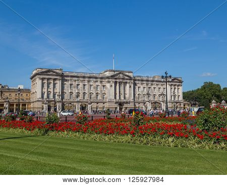 LONDON UK - 18TH JULY 2015: The outside of Buckingham Palace in London during the summer showing the buildings and flowers. People can be seen outside.