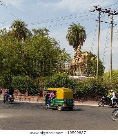 AGRA INDIA - 25TH MARCH 2016: Traffic along streets of Agra during the day. Tuk Tuk Rickshaws motorbikes and a statue can be seen.