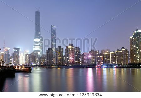 The Lujiazui Pudong area of Shanghai China at night reflecting off of the Huangpu River