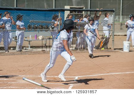 Filipino softball batter running to first base.