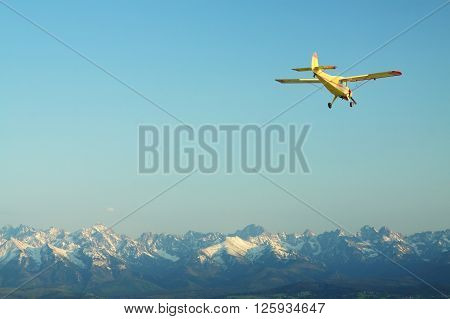 Small yellow aircraft over panorama of mountains