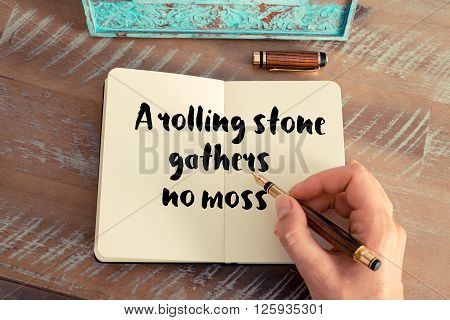 Handwritten quote A rolling stone gathers no moss, as inspirational concept image