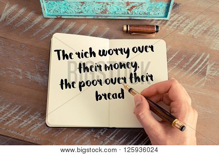 Handwritten quote The rich worry over their money the poor over their bread, as inspirational concept image