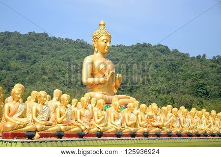 Big Golden and thousand of Golden Buddha statues with green mountain background