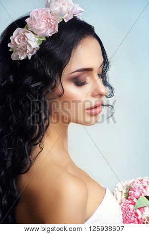 Beautiful young girl with a floral ornament in her hair on a blue background.Portrait of a beautiful woman in a wedding dress in the image of the bride. Picture taken in the studio. Portrait of beautiful bride. Wedding dress. Wedding decoration